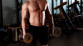 Młody człowiek ćwiczy z ciężarem w gym obraz stock