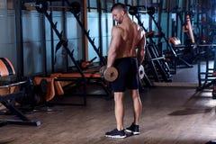 Młody człowiek ćwiczy z ciężarem w gym zdjęcie stock