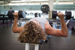 Młody człowiek ćwiczy z dumbbells w gym Fotografia Royalty Free
