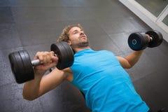 Młody człowiek ćwiczy z dumbbells w gym Zdjęcia Royalty Free