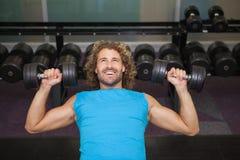 Młody człowiek ćwiczy z dumbbells w gym Fotografia Stock