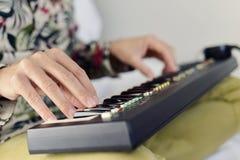 Młody człowiek bawić się elektroniczną klawiaturę Obraz Stock
