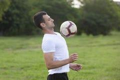 Młody człowiek bawić się futbol w parku utrzymuje balowym w powietrzu obraz royalty free