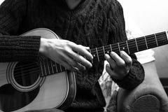 Młody człowiek bawić się gitarę akustyczną na tle betonowa ściana obrazy royalty free