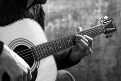 Młody człowiek bawić się gitarę akustyczną na tle betonowa ściana Zdjęcie Stock