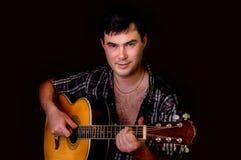 Młody człowiek bawić się gitarę akustyczną - odizolowywającą na czerni Fotografia Royalty Free