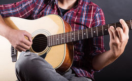 Młody człowiek bawić się gitarę akustyczną w studiu zdjęcia stock