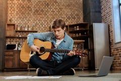 Młody człowiek bawić się gitarę i czytania muzycznego prześcieradło Obraz Royalty Free