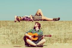 Młody człowiek bawić się gitarę jego dziewczyna nadmorski Fotografia Royalty Free