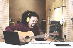 Młody człowiek bawić się gitarę w muzycznym studiu Obrazy Stock