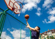 Młody człowiek bawić się koszykówkę Zdjęcia Royalty Free