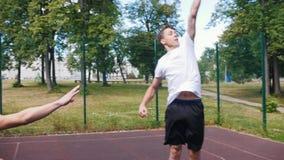 Młody człowiek bawić się koszykówkę outdoors z przyjacielem, drybluje cel od daleko i zdobywa punkty, zbiory wideo
