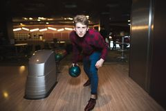 Młody człowiek bawić się kręgle z błękitną piłką dla rzucać kulą Mężczyzna rzuca pociska na kiju Fotografia Royalty Free