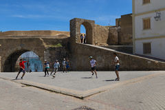 Młody człowiek bawić się piłkę nożną w kwadracie blisko do ścian forteca Portugalski miasto Cytuje Portugaise w miasteczku El obrazy stock