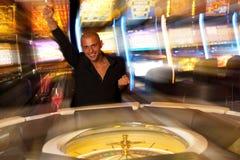 Młody człowiek bawić się ruletę w kasynie zakłada się pieniądze i wygrywa Zdjęcia Royalty Free