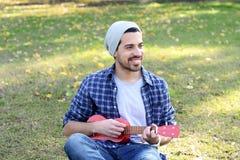 Młody człowiek bawić się ukelele w parku Fotografia Royalty Free