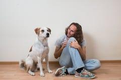 Młody człowiek bawić się z jego psem w domu Obraz Stock