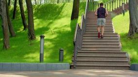 Młody człowiek biega na piętrze w zwolnionym tempie Młodych człowieków działający up schodki przy parkiem zdjęcie wideo