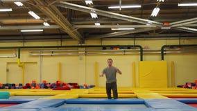 Młody człowiek biega wzdłuż trampoline kompleksu i skacze wysoko up zbiory