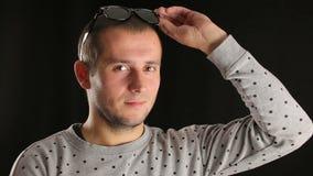 Młody człowiek bierze daleko okulary przeciwsłonecznych i patrzeć w obiektyw zbiory