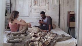 Młody człowiek bierze fotografię kobieta w piżamach na film kamerze Multiracial pary obsiadanie na łóżku w ranku zbiory