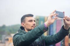 Młody człowiek bierze fotografię z jego telefonem na dachu zdjęcia royalty free
