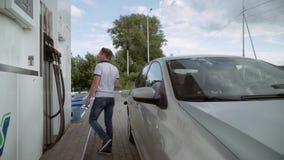Młody człowiek bierze krócicę z benzynowego zbiornika i wraca je miejsce zbiory wideo