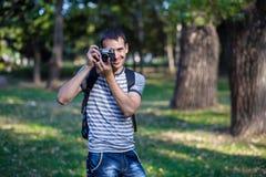 Młody człowiek bierze obrazki na retro kamerze fotografia stock