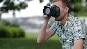 Młody Człowiek Bierze obrazki Przy Fachową Cyfrowego SLR kamerą zbiory wideo