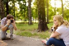 Młody człowiek bierze strzałowi pięknej kobiety z psem w pogodnym lato parku Data lub chodzić obraz royalty free