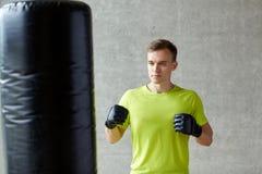 Młody człowiek boksuje z uderzać pięścią torbę w rękawiczkach Zdjęcie Royalty Free