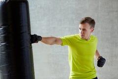 Młody człowiek boksuje z uderzać pięścią torbę w rękawiczkach Obrazy Stock