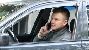 Młody człowiek ciągnie na drodze opowiadać na jego telefonie komórkowym Biznesmen w samochodowym mówieniu na smartphone Zdjęcia Stock