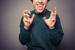Młody człowiek ciągnie niemądre twarze fotografia stock