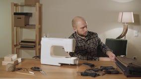 Młody człowiek ciągnie out pudełko nici i igły Pracować jako krawczyna i używać szwalną maszynę w tekstylnym studiu zbiory