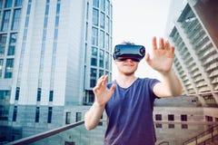Młody człowiek cieszy się rzeczywistość wirtualna szkieł słuchawki lub 3d widowiska stoi przeciw nowożytnemu miasto budynku tłu o Zdjęcie Royalty Free