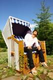 Młody człowiek cieszy się słońce opiera na łozinowym krześle Zdjęcia Royalty Free