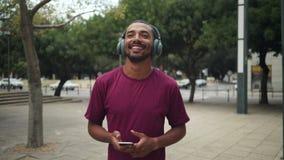 Młody człowiek cieszy się słuchać muzyka podczas gdy chodzący na miasto ulicie zbiory