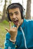 Młody człowiek cieszy się słuchać muzyka rockowa Fotografia Royalty Free