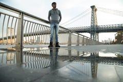 Młody człowiek czeka wzdłuż Wschodniej rzeki pod Williamsb, Obrazy Royalty Free