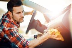 Młody człowiek czyści jego samochód outdoors Obrazy Stock