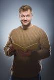 Młody człowiek czyta książkę i ono uśmiecha się na popielatym tle fotografia stock