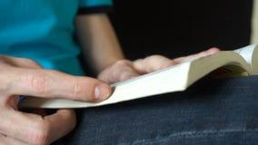 Młody człowiek czyta książkę, leafing przez stron, zwolnione tempo zdjęcie wideo