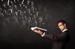 Młody człowiek czyta książkę z znakami zapytania nadchodzącymi out od go Fotografia Stock