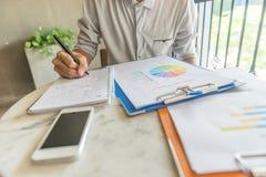 Młody człowiek czyta pieniężnych dane na dokumencie i pisze notatkach obraz stock