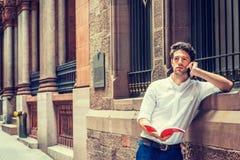 Młody człowiek czytelnicza książka, opowiada na telefonie komórkowym outside w Nowym Yor Zdjęcie Royalty Free