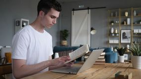 Młody Człowiek Czytelnicza książka podczas gdy Siedzący na biurku zbiory wideo