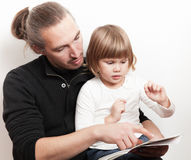 Młody człowiek czytelnicza książka z małą Kaukaską dziewczyną Obraz Stock