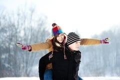 Młody człowiek daje jego dziewczynie piggyback przejażdżce Obrazy Royalty Free