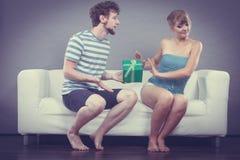 Młody człowiek daje obrażającemu kobieta prezenta pudełku fotografia royalty free